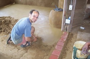 Tony Sirna, intern supervisor, installing an earthen floor