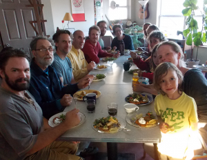 The newly-formed kitchen co-op sits down to a shared meal in Dancing Rabbit's Common House. Photo by Kurt.