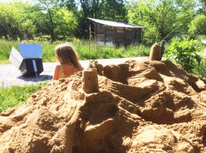 Katherine slows down and takes a break from preparing lunch to build sandcastles with Althea. Photo by Katherine.