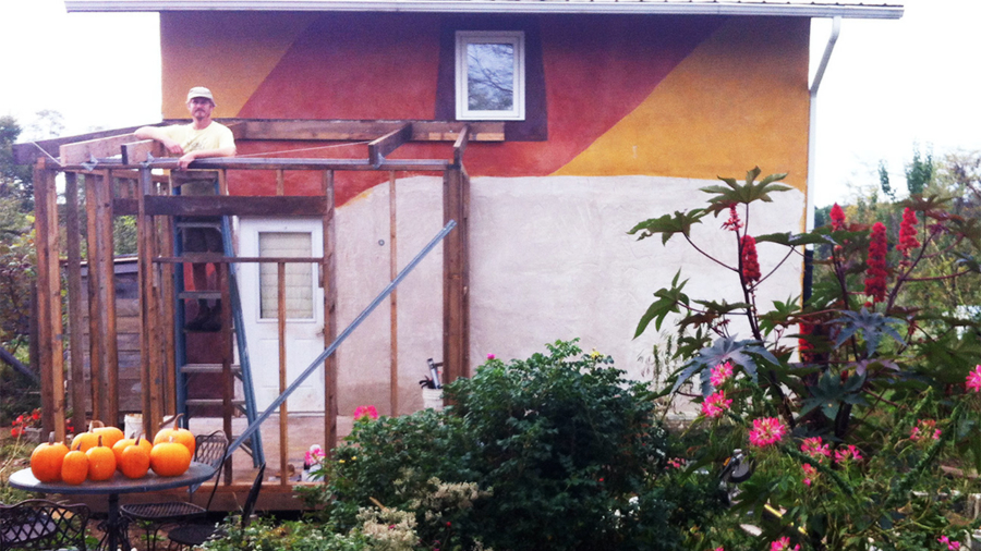 Dan working on his porch addition as pumpkins look on. Photo by Ted.