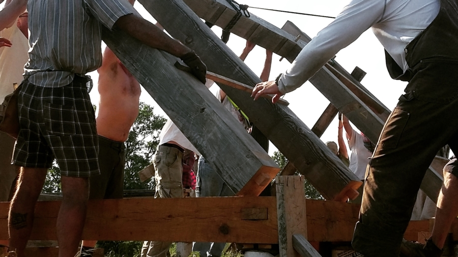 Thomas, Brian, and other workshop participants raise a bent on the new goat barn. Photo by Ben B.