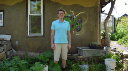 Avi, in the permaculture gardens, outside of Ironweed Kitchen where he does cheese making.