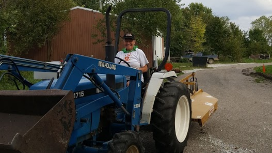 Cat showing off one of her newest skills: driving our co-op owned tractor.