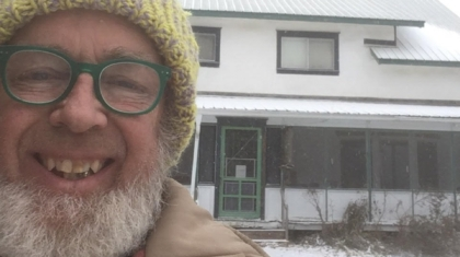 Farmer John enjoying a snowy day in front of our eco inn, the Milkweed Mercantile.