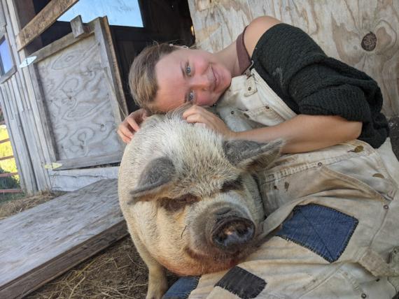 Emeshe embracing a pig